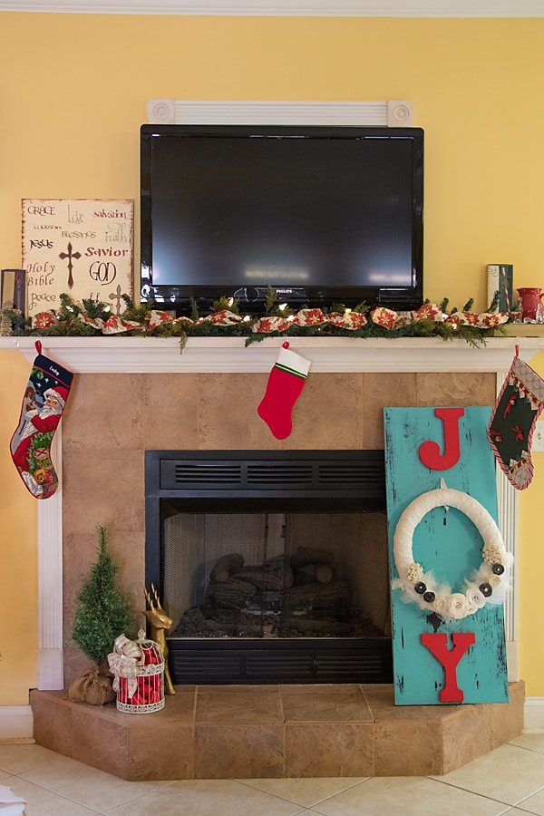 Mantel and hearth with faux greenery and distressed wood joy sign