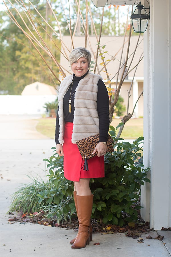 winter skirt outfit with tall boots and faux fur vest