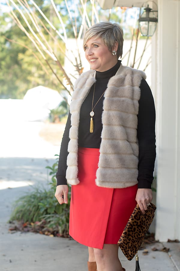 faux fur vest with red skirt and black sweater