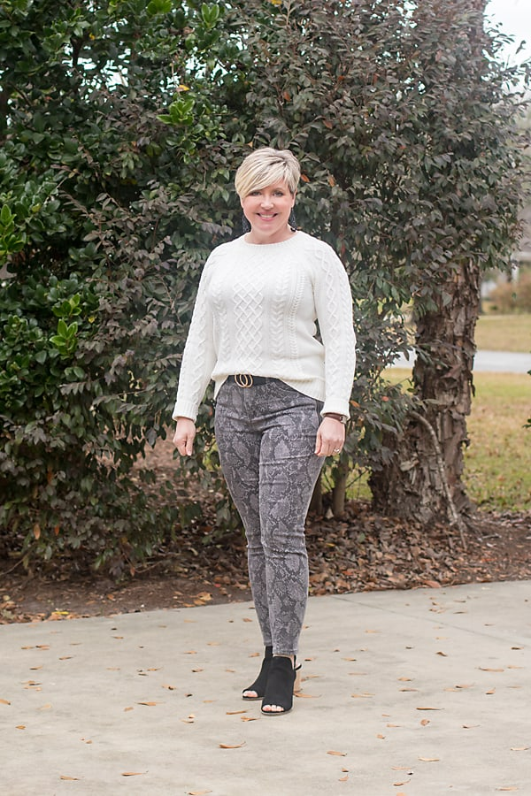 front tuck a chunky sweater paired with snakeskin jeans to break out of a winter style rut