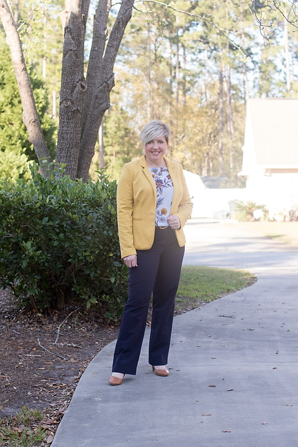 mustard blazer with navy pants and floral blouse