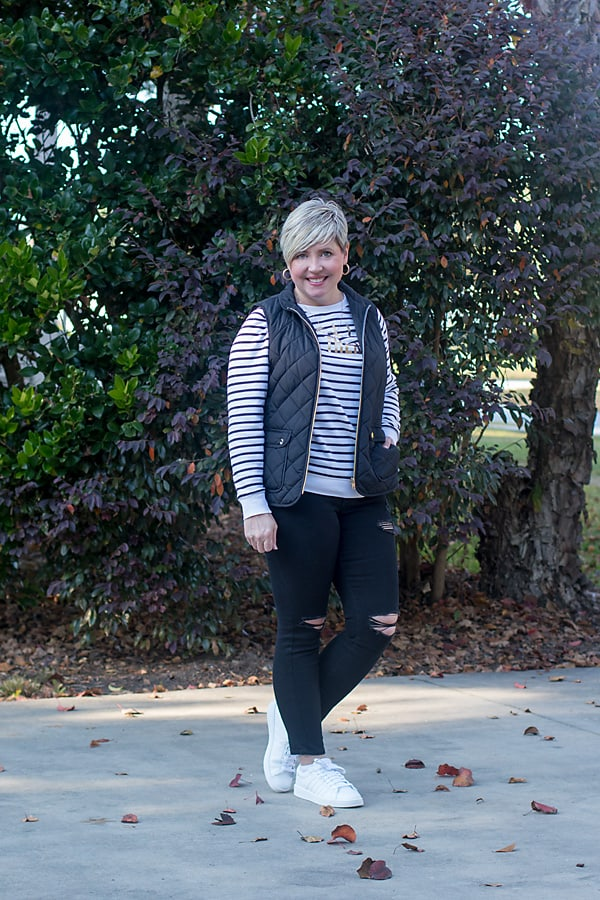 quilted vest with distressed jeans and sneakers outfit
