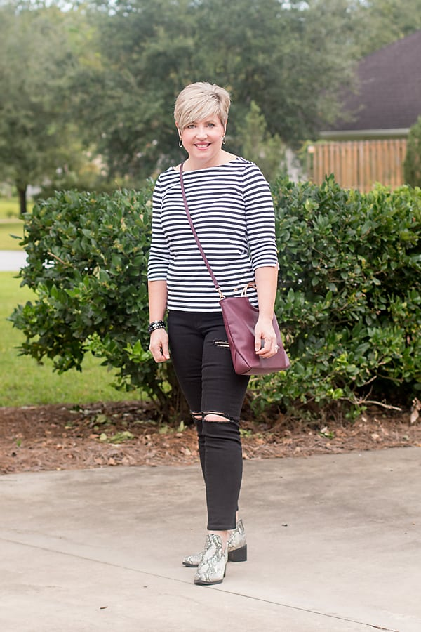womens fall outfit with snakeskin boots and black jeans