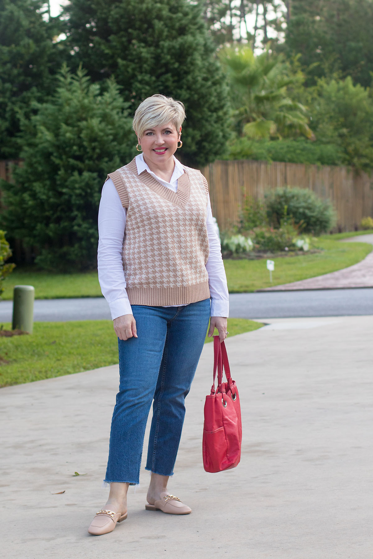 fall fashion trends for women over 40; sweater vest and straight leg jeans outfit